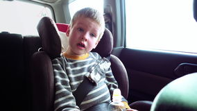 Netter Junge in einem Kinderautositz schaut heraus das Fenster stock video