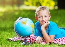 Netter Junge in einem Park mit einer Kugel Stockbild