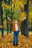 Netter Junge geht und wirft in einem bunten Herbst Park auf lizenzfreie stockfotos