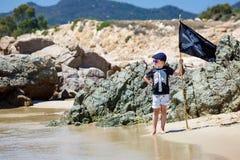 Netter Junge gekleidet als Pirat auf Strand Stockfoto