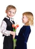 Netter Junge gibt dem Mädchen Tulpen Lizenzfreie Stockbilder