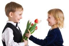 Netter Junge gibt dem Mädchen Tulpen Stockfotos