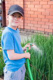 Netter Junge gießt Frühlingszwiebeln Schnitt-Schlauch Stockbilder