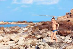Netter Junge mit Bambusstange täuscht vor, wie er Ureinwohner auf einsamer Insel ist stockfoto