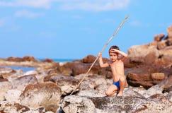 Netter Junge mit Bambusstange täuscht vor, wie er Ureinwohner auf einsamer Insel ist lizenzfreie stockbilder