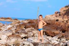 Netter Junge mit Bambusstange täuscht vor, wie er Ureinwohner auf einsamer Insel ist stockbild
