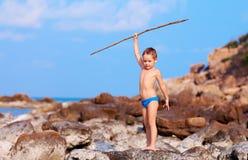 Netter Junge mit Bambusstange täuscht vor, wie er Ureinwohner auf einsamer Insel ist stockfotos