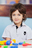 Netter Junge mit Blöcken auf Schreibtisch am Kindergarten lizenzfreie stockfotos