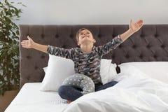 Netter Junge mit dem Spielzeug, das nach Schlaf ausdehnt lizenzfreie stockfotos