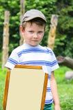 Netter Junge mit einem hölzernen Schild und einer Klinge Stockfoto