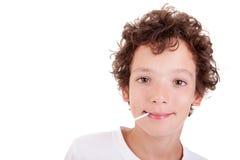 Netter Junge mit einer Süßigkeit auf dem Mundlächeln Stockfotografie