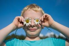 Netter Junge mit Gänseblümchen auf den Augen, die Spaß haben Stockfotos