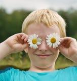 Netter Junge mit Gänseblümchen auf den Augen, die Spaß haben Stockbild