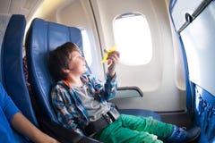Netter Junge mit Spielzeugfläche sitzen durch das Flugzeugfenster Stockfoto