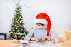 Netter Junge rollt Teig für Weihnachtsplätzchen Stockfotografie
