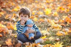 Netter Junge, sitzend auf Rasen, Herbsttag und essen Pfannkuchen Lizenzfreie Stockfotografie