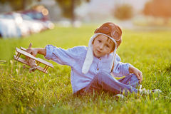 Netter Junge, spielend mit Flugzeug auf Sonnenuntergang im Park Lizenzfreies Stockfoto