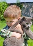 Netter Junge umarmt Katze Lizenzfreie Stockfotografie