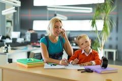 Netter Junge und Frau sitzen am Schreibtisch im Büro Lizenzfreie Stockbilder
