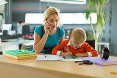 Netter Junge und Frau sitzen am Schreibtisch im Büro Lizenzfreie Stockfotos