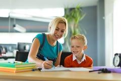 Netter Junge und Frau sitzen am Schreibtisch im Büro und im abgehobenen Betrag Stockbild