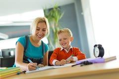 Netter Junge und Frau sitzen am Schreibtisch im Büro und im abgehobenen Betrag Stockfotos
