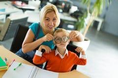 Netter Junge und Frau sitzen am Schreibtisch im Büro und im Spiel Stockbild