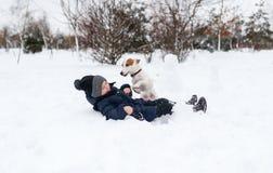 Netter Junge und Hund, die im Schnee spielt stockbilder