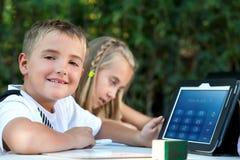 Junge, der draußen Hausarbeit auf Tablette zeigt. Lizenzfreie Stockfotos