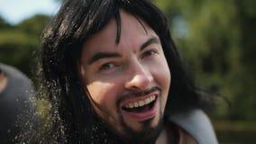 Netter junger b?rtiger Mann mit dem langen Haar und gef?lschtem Muskelkost?m singt drau?en stock footage