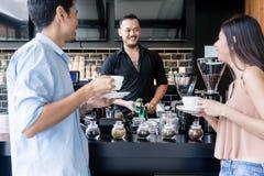 Netter junger Barmixer, der die Kaffeemaschine bei der Unterhaltung säubert stockfotografie