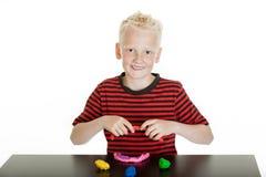 Netter junger blonder Junge, der mit Kitt modelliert Lizenzfreies Stockbild