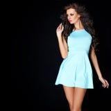 Netter junger Brunette, der im blauen Kleid aufwirft Stockfotos