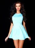 Netter junger Brunette, der im blauen Kleid aufwirft Stockfotografie