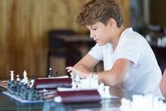 Netter junger intelligenter Junge im blauen Hemd spielt Schach auf dem Training vor dem Turnier Schachsommerlager liebhaberei lizenzfreies stockbild