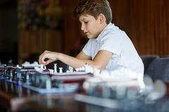Netter junger intelligenter Jungenjugendlicher im weißen Hemd spielt Schach auf dem Training vor dem Turnier Schachsommerlager Ho lizenzfreie stockbilder