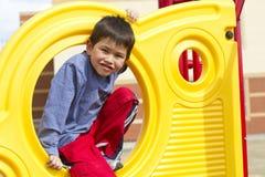 Netter junger Junge, der auf Spielplatzausrüstung spielt Lizenzfreies Stockfoto