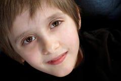 Netter junger Junge, der oben an der Kamera lächelt lizenzfreie stockfotos