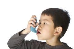 Netter junger Junge, der seinen Asthmainhalator verwendet Lizenzfreie Stockfotografie