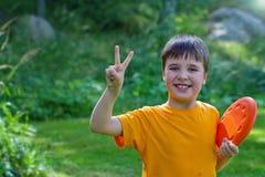 Netter junger Junge mit einem Frisbee Stockfoto