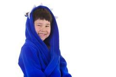 Netter junger Junge mit großem Lächeln im Bademantel Stockbild