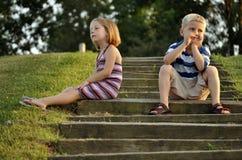 Netter junger Junge und Mädchen, die auf Jobstepps des Parks sitzt Lizenzfreie Stockfotografie