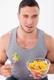 Netter junger Kerl schmeckt Salat mit Vergnügen Stockfotografie