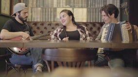 Netter junger lächelnder bärtiger Mann, der Gitarre in der Stange, sein Freund spielt Akkordeon während entzückende pralle Frau s stock video footage