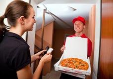 Netter junger Lieferbote, der einen Pizzakasten hält, während Sie auf Weiß lokalisiert werden Lizenzfreie Stockfotos