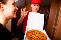 Netter junger Lieferbote, der einen Pizzakasten hält, während Sie auf Weiß lokalisiert werden Stockfoto