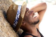 Netter junger Mann, der über den Strand mit Hut lacht Lizenzfreies Stockbild