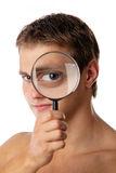 Netter junger Mann, der durch ein Vergrößerungsglas schaut lizenzfreies stockfoto