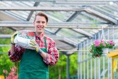 Netter junger Mann, der eine Tasche des Pottingbodens beim Arbeiten trägt Stockbild