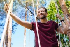 Netter junger Mann, der an einem Seilpark klettert lizenzfreie stockfotos